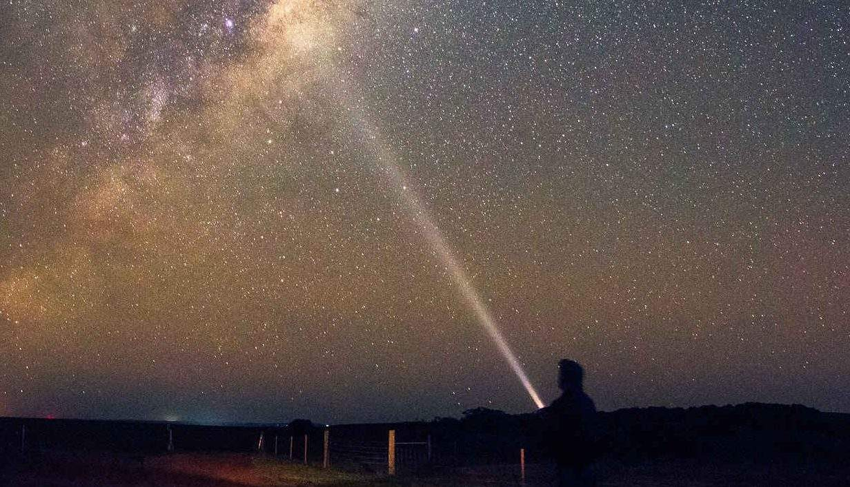 Man shining torch at stars